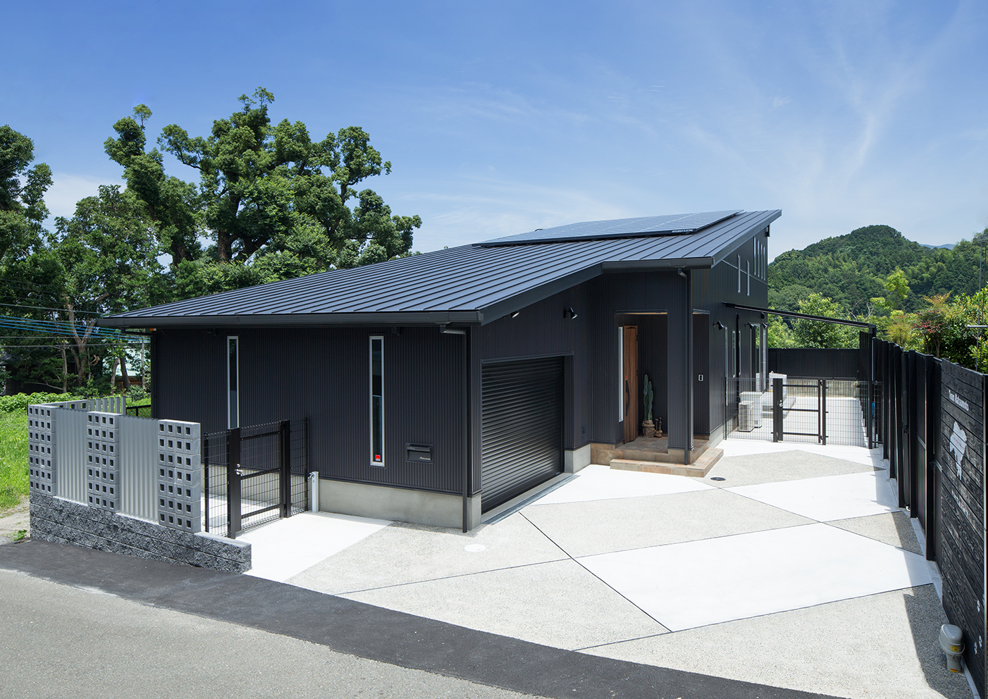 外観(南西側) インナーガレージと玄関までのアプローチはシンプルなコンクリートの洗い出し仕上げです。